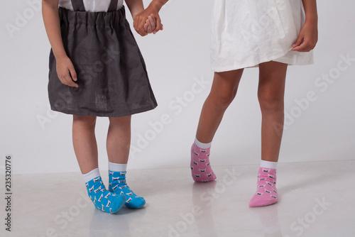 legs of two little girlfriends in knitted socks in a white studio