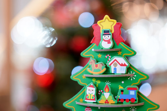 Christmas tree paper craft decoration on the wood table with blur big Christmas tree behide.