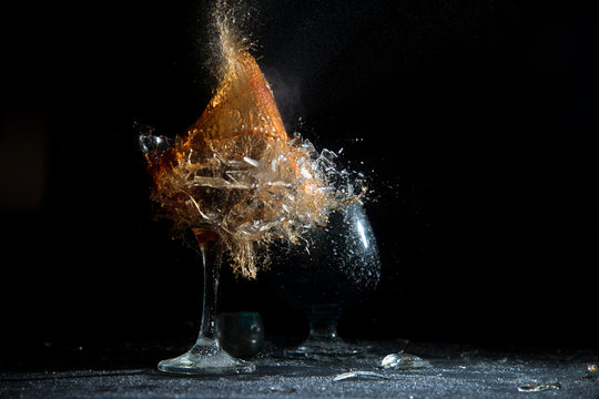 The breaking of a glass with fragments. The explosion of a glass on a black background with a colored liquid. Splashes of colors.
