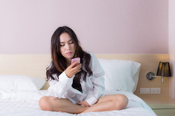 Woman use cell phone on the bed.