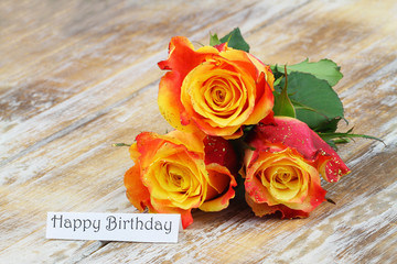 Happy birthday card with three beautiful colorful roses on rustic wooden surface