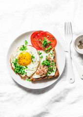 Healthy breakfast or brunch - fried egg, fresh tomatoes and smoked mackerel toast on a light background, top view