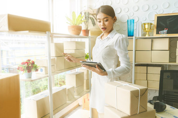 Young Asian woman using digital tablet checklist Orders online from customers at home while Delivery arrangements postal parcel. ,startup small business entrepreneur SME distribution warehouse concept
