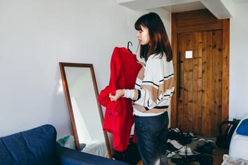 鏡の前で服を合わせる女性