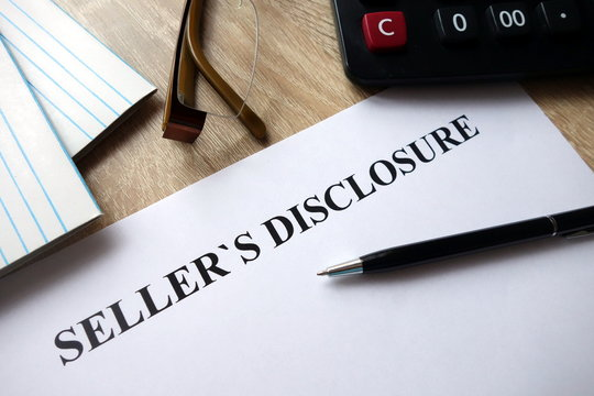 Seller`s disclosure statement with pen, calculator and   glasses in office