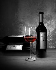 Stilleben mit einer Flasche und einem Glas Rotwein im Bordeaux Stil im Weinkeller