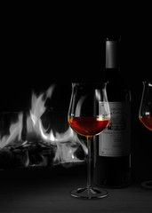 Stilleben mit einer Flasche und einem Glas Rotwein im Bordeaux Stil vor gemütlichem Kamin Feuer