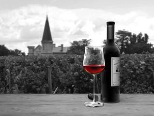 """Stilleben mit einer Flasche und einem Glas Rotwein im Bordeaux Stil mit einem """"Château"""" und einem Weinberg im Hintergrund"""
