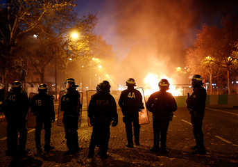 """Police officers stand guard on the Champs-Elysees during a """"Yellow vest"""" protests against higher fuel prices, in Paris"""