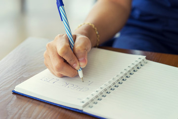 Woman hand writing check list on notebook, planning concept.