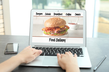 Woman using laptop to order food delivery at home