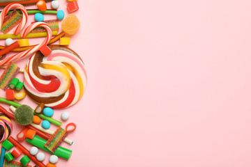Flat lay composition with different yummy candies and space for text on color background