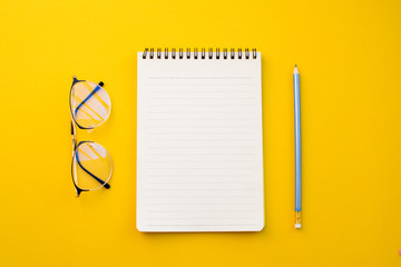 empty paper of notebook eyeglasses and pencil on yellow background with school concept.