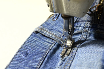 Stitching, stitching a hole in blue jeans with a sewing machine. Part of sewing machine and jeans cloth closeup. Tailoring