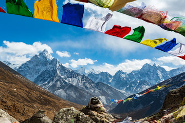 Fototapeta Nepal. From Lukla to Everest. Walk to Everest base camp. Square memorial to the fallen climbers. In the foreground are stones and Nepalese prayer flags, on the horizon of the mountain. obraz