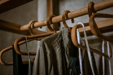 Boho chic open wardrobe, clothing rack, rattan wooden hangers, Fashion blogging concept, neutral colors. Loft bedroom interior design.