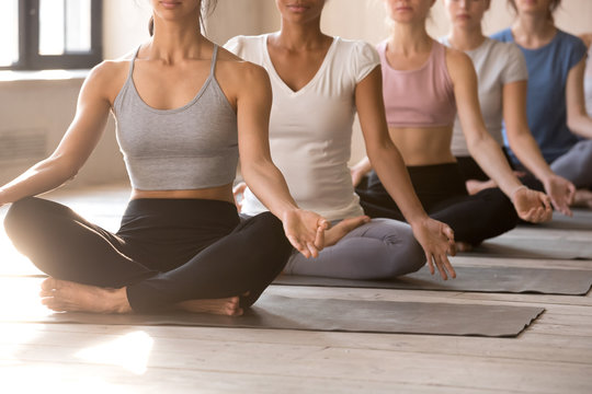 Group of young diverse people practicing yoga lesson, doing Easy Seat exercise, Sukhasana pose, sporty female students working out indoor at club or yoga studio. Well being, wellness concept, close up