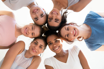 Diverse group of sporty attractive girls enjoy time together, smiling people in sportswear after...