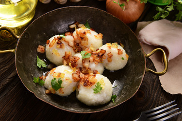 Meat stuffed potato dumplings with fried onion  and greaves on top