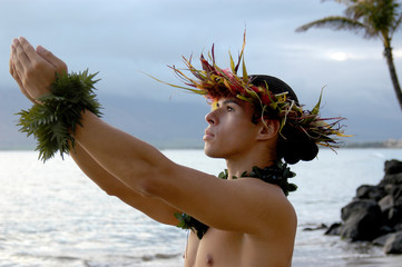 Male Hula Dance performs on the beach with expressive hand movements.