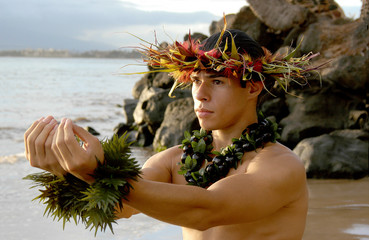 Male Hula Dancer poses on the beach in a hula dance.