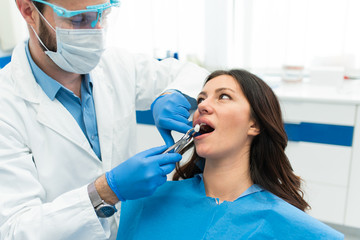 Beautiful successful dentist fixing cavity teeth on a woman patient sitting in the dentist office chair. Stomatology concept.
