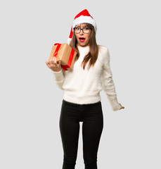 Girl with celebrating the christmas holidays surprised because has been given a gift on isolated grey background