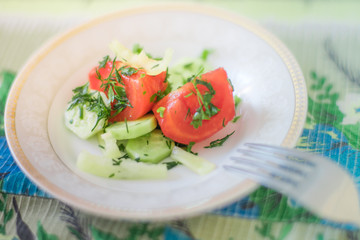 salad with fresh tomato, cucumber, pepper and greens on a white saucer with a fork.