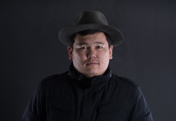 classic portrait of asian man in hat on black studio background