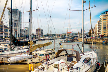 De Haan, Kingdom of Belgium. Sailboats and yachts parking in a marina under blue sunny sky at De Haan. Buildings. City.