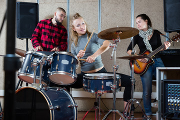 Music band with positive girl drummer rehearsing