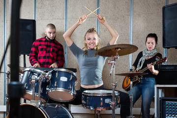 Music band with glad girl drummer rehearsing