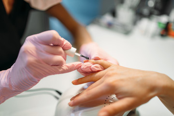 Beautician applying nail varnish to female client