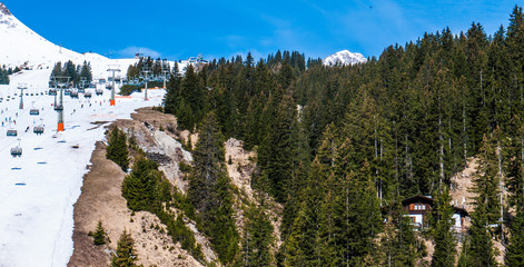 Open Ski Slope with skiers - taken in Lech, Austria. With mountain peaks in the background and pine forest.