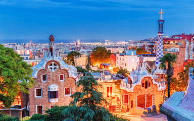 Captivating view of Park Guell, international landmark in Barcelona, Spain, Europe. UNESCO heritage site, beautiful dusk scene of illuminated city. Famous and popular travel destination.