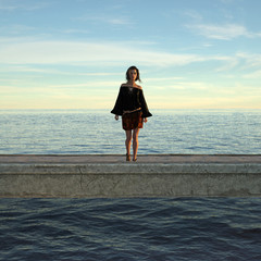 3d illustration of a woman wearing a dress standing on a seaside jetty in the late afternoon light.