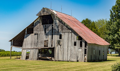 An aging and decaying wooden barn in a rural area.