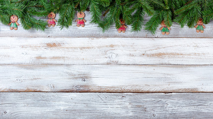 Christmas evergreen branches and cookies on white vintage wooden planks