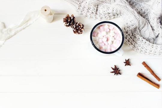 Christmas styled composition. Hot chocolate, marshmallow,cinnamon sticks, anise stars, pine cones and knitted blanket on white wooden table background. Winter breakfast concept. Flat lay, top view.