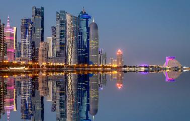 Die Skyline der West Bay von Doha, Qatar, am Abend mit Reflektionen in der Bucht