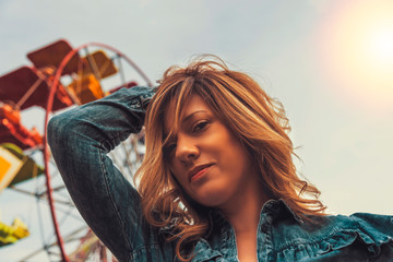 Lovely young woman in a Luna Park shortly before sunset in autumn