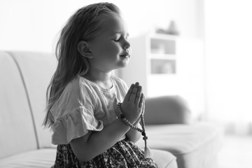 Cute little girl with beads praying on sofa in living room, black and white effect. Space for text