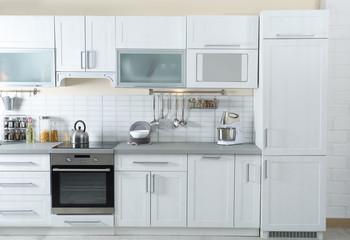Stylish kitchen interior with modern refrigerator and furniture