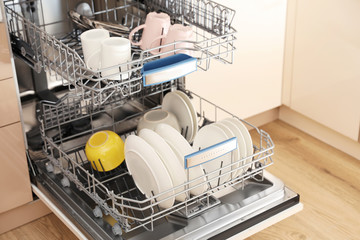 Open dishwasher with clean tableware in kitchen