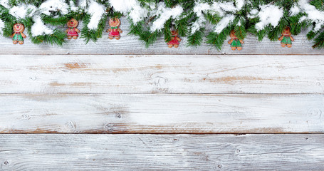 Snowy Christmas evergreen branches and cookies on white vintage wooden planks