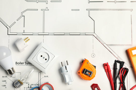 Flat lay composition with electrician's tools on house plan. Space for text
