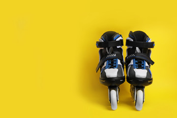 Pair of inline roller skates on color background. Space for text