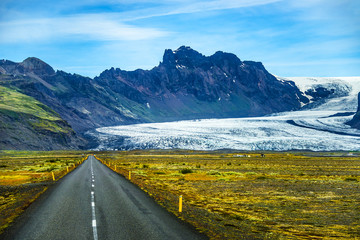 Icelandic colorful landscape on Iceland with glacier tongue, green moss and isolated road, summer time