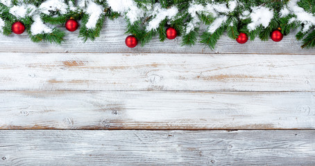 Snowy Christmas evergreen branches and red ornaments on white vintage wooden planks