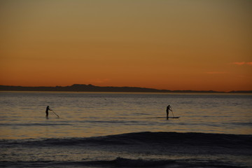 Paddle boarder on ocean at dusk